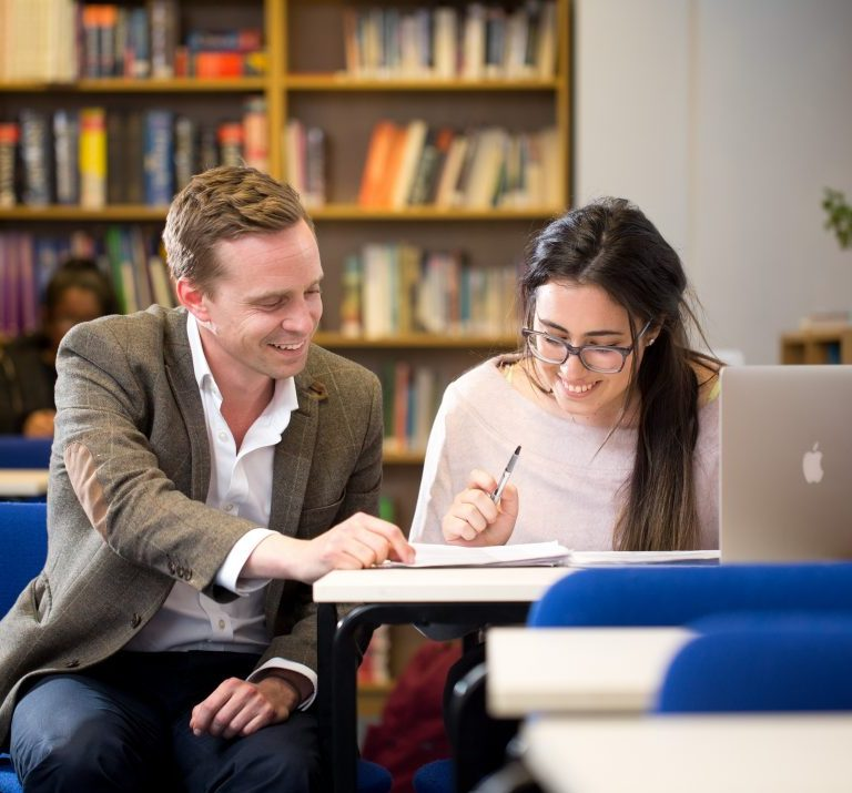 A teacher helping a student in the library