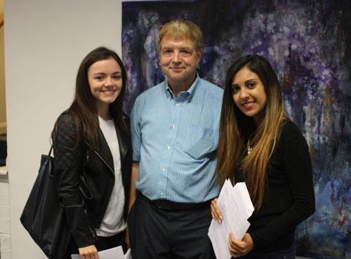 Tara McCaul and Janu Shah celebrating their A* results with Peter.
