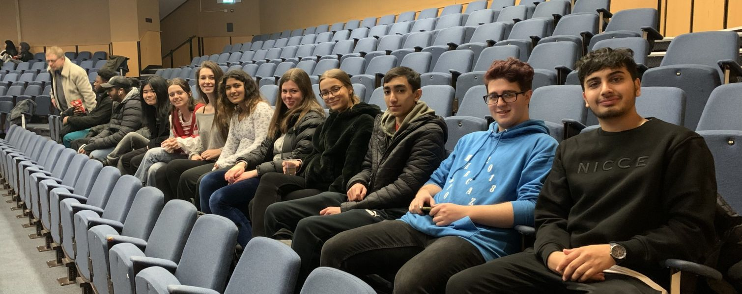 Students smiling as they're sat in an auditorium