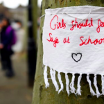 sign on tree with message: girls should feel safe at school
