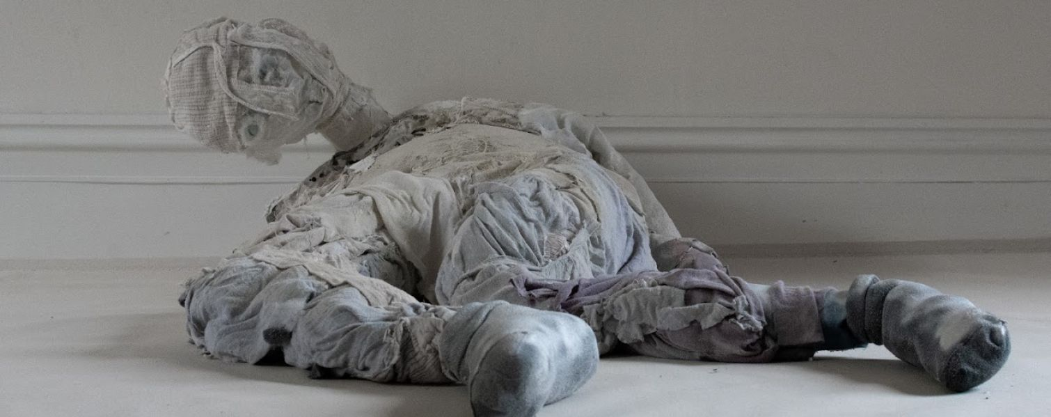 sculpture of a figure on floor made of material