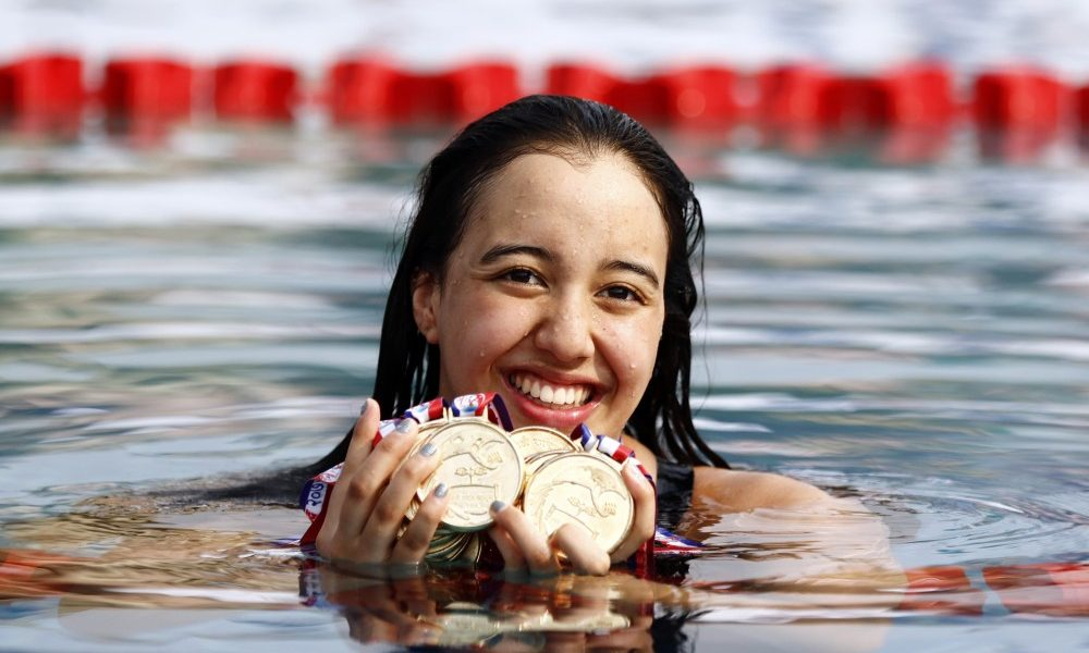 girl in pool with swimming medals