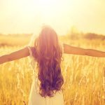 girl in field with outstretched arms